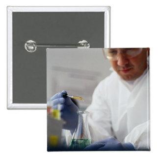 Chemist Measuring Drops into a Flask Button