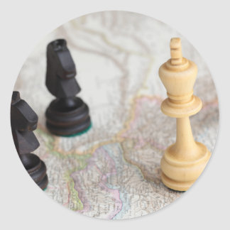 Chess figures on a map classic round sticker