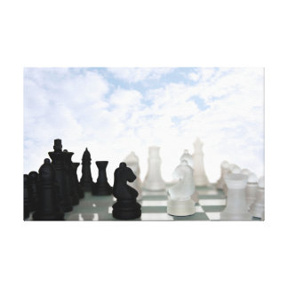 chess pieces isolated against cloudy sky canvas print
