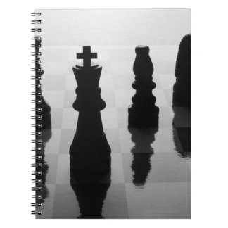 Chess pieces on chess board in black and white notebook