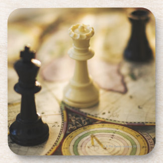 Chess pieces on old world map beverage coaster