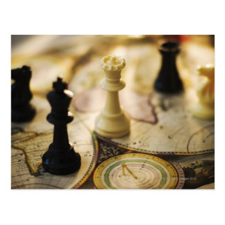 Chess pieces on old world map postcard