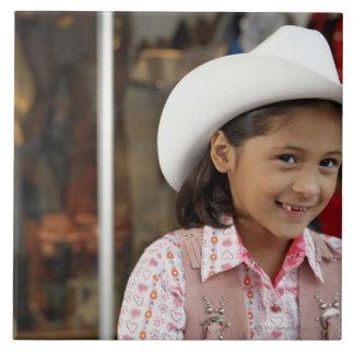 Chica (8-10) stetson que lleva, sonriendo azulejo cuadrado grande