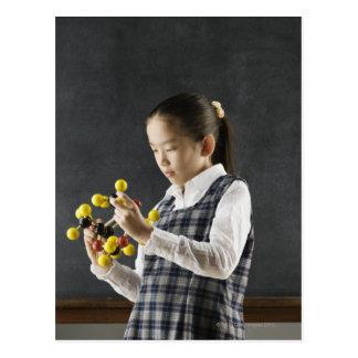 Chica asiático que mira el modelo de la molécula postales
