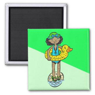 Chica con el juguete de la piscina imán cuadrado