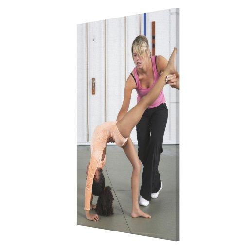 chica de ayuda del instructor con sus ejercicios d lienzo envuelto para galerias