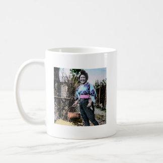 Chica de granja sonriente en viejo japonés del taza