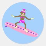 Chica de la persona que practica surf del mono del etiquetas redondas