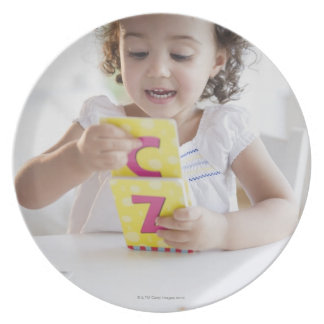 Chica de la raza mixta que juega con las tarjetas platos de comidas