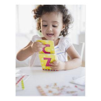 Chica de la raza mixta que juega con las tarjetas postales