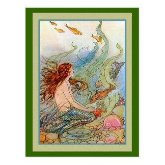 Chica de la sirena en el mar con los pescados y postales