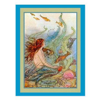 Chica de la sirena en el mar con los pescados y tarjeta postal