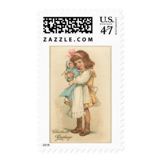 Chica de los saludos del navidad del vintage con sello postal
