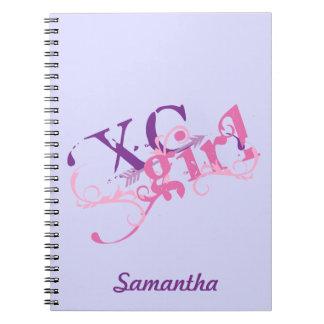 Chica del campo a través - XC con la flecha Cuaderno