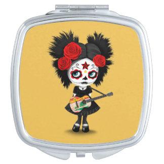 Chica del cráneo del azúcar que toca la guitarra espejos maquillaje