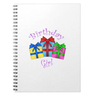 Chica del cumpleaños en púrpura con los presentes libreta espiral