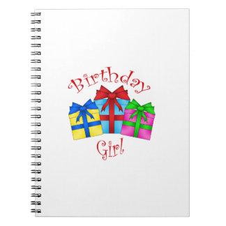 Chica del cumpleaños en rojo con los presentes libretas