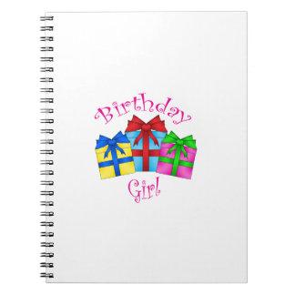Chica del cumpleaños en rosa con los presentes cuaderno