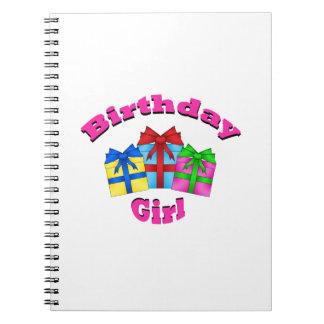 Chica del cumpleaños en rosa con los presentes libros de apuntes
