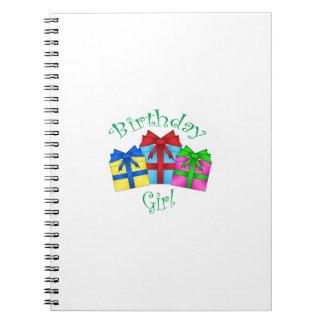Chica del cumpleaños en verde con los presentes libro de apuntes con espiral