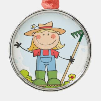 Chica del granjero con un rastrillo en hierba adorno navideño redondo de metal