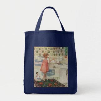 Chica del vintage, niño que hace la ropa colgante bolsa tela para la compra