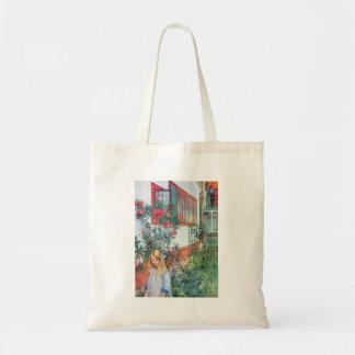 Chica en el jardín con las flores rojas bolsas