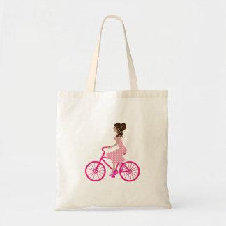 Chica en la bici rosada que lleva un vestido