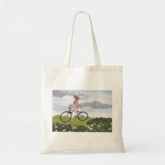 Chica en la bolsa de asas de la bicicleta