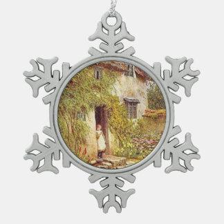 Chica en la entrada de la cabaña del país del adorno de peltre en forma de copo de nieve