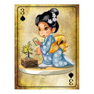 Chica japonés en el kimono que riega un árbol de postales