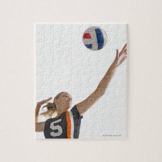 Chica joven (16-17) que juega a voleibol rompecabezas con fotos