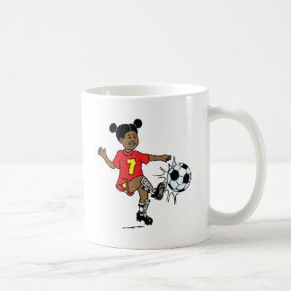 Chica joven que juega a fútbol taza