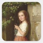 Chica joven que se coloca en una entrada que hace pegatina cuadrada