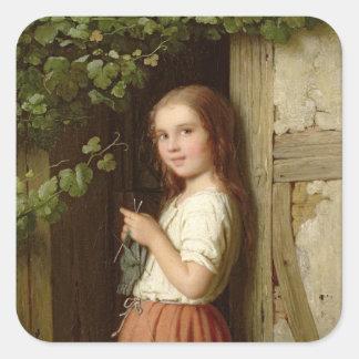 Chica joven que se coloca en una entrada que hace pegatina cuadradas