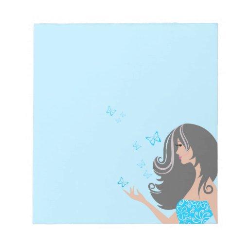 Chica lindo con la libreta azul de las mariposas blocs de notas