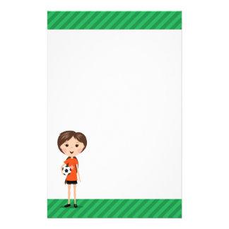 Chica lindo del fútbol del dibujo animado que sost papelería de diseño