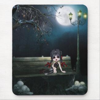 Chica lindo del gótico en banco por las pilas de c tapete de ratones