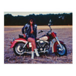 Chica modelo clásico en una motocicleta postal