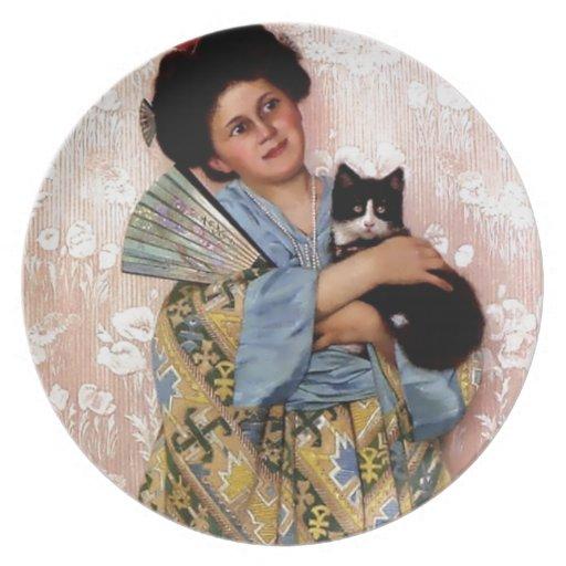 Chica oriental con un gato del mascota plato de cena