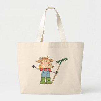 Chica que cultiva un huerto que agita un saludo bolsas de mano