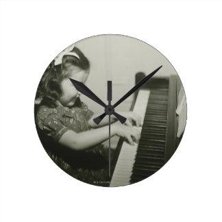 Chica que juega el piano reloj redondo mediano