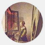 Chica que lee una letra en una ventana abierta, po etiqueta redonda