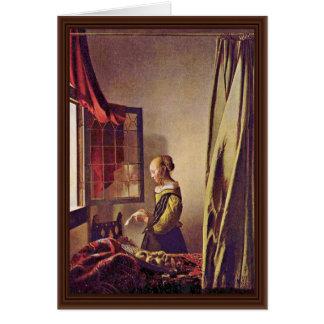 Chica que lee una letra en una ventana abierta, po tarjetón