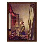 Chica que lee una letra en una ventana abierta, po tarjetas postales