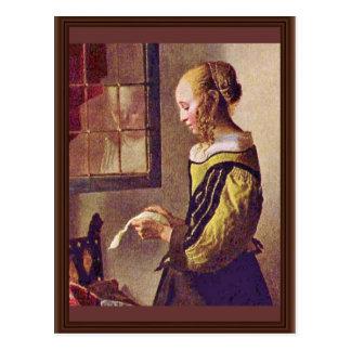 Chica que lee una letra en una ventana abierta tarjetas postales