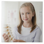 Chica que lleva a cabo el modelo de la espina dors azulejo cuadrado grande