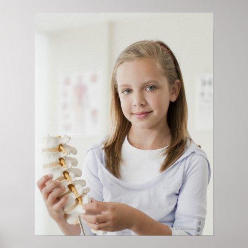 Chica que lleva a cabo el modelo de la espina dors póster