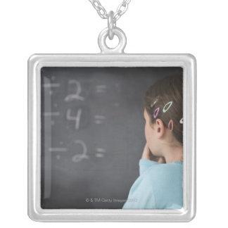 Chica que mira ecuaciones de la matemáticas en la colgante cuadrado