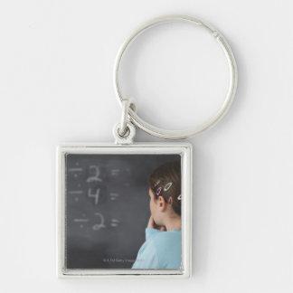 Chica que mira ecuaciones de la matemáticas en la llavero cuadrado plateado